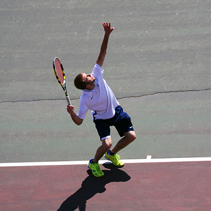Male tennis player serving the ball