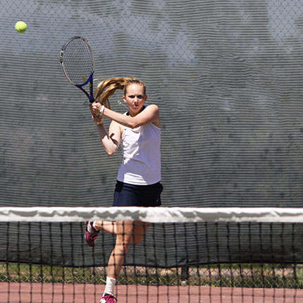 Female tennis player with the net in the foreground