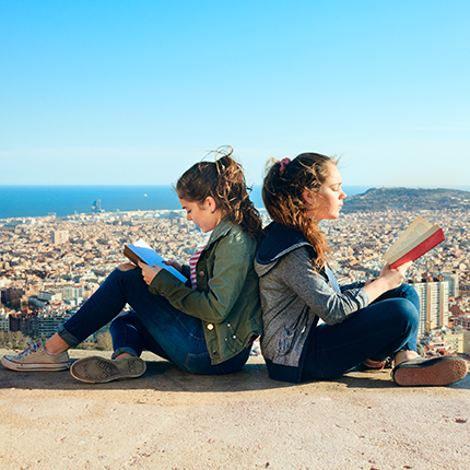 Girls sitting back to back reading books, overseeing a european looking city