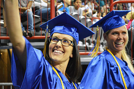 A smiling graduate waving to the crowd