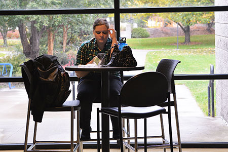 Student reading at a table
