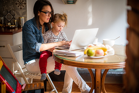 mom on computer with daughter in lap