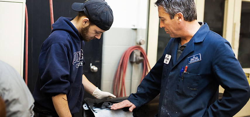 An instructor and gloved student work on refinishing a body panel