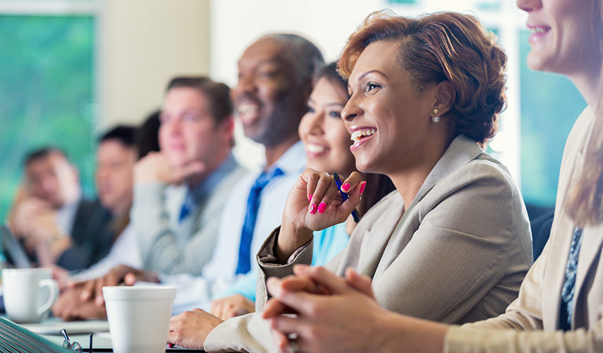 A smiling woman takes notes at a meeting with her colleagues