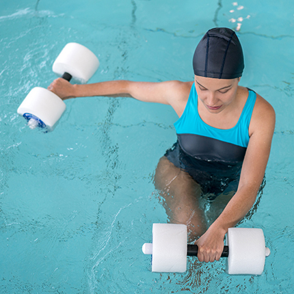 Woman doing weight training exercises in pool.
