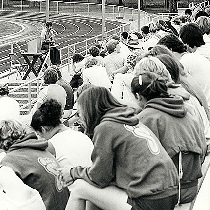 Black and white photo of CCS audience listening to a speaker on the track field.
