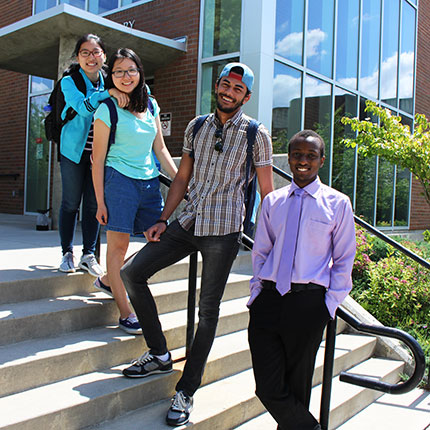 Group of students standing on outdoor stairs leaning against the railing