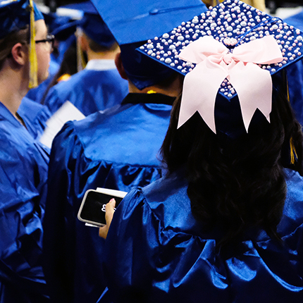 a graduation cap decorated with a bow and pearls