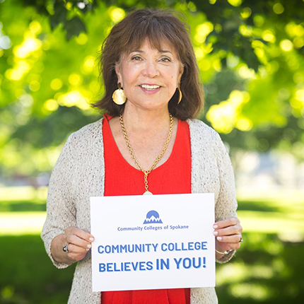 "Chancellor Christine Johnson holding a sign that says ""Community College Believes in you."" Behind are lush green trees."