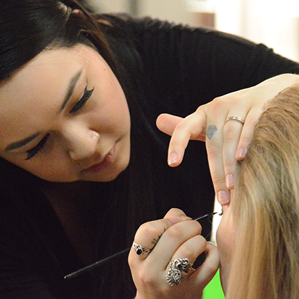 SCC cosmetology student applying make-up