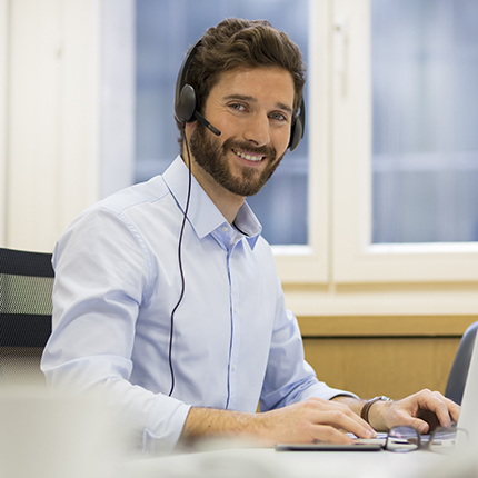Man wearing a headset at a computer