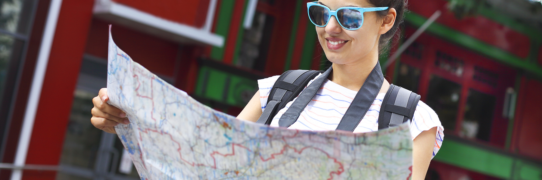 girl with sunglasses holding a map