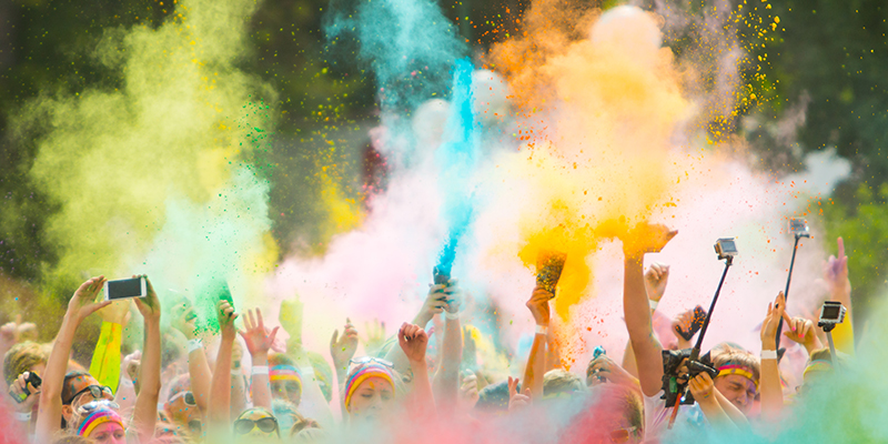 Runners ata color run, throwing powdered color in the air