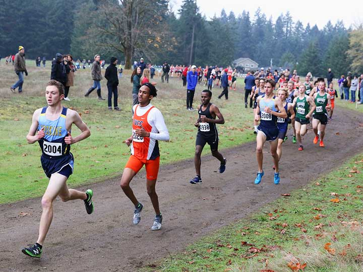 Men's cross country team running with the group