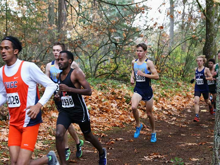 Men's cross country team running on dirt path