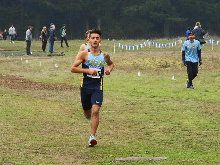 Men's cross country team running on grass with coach in the background