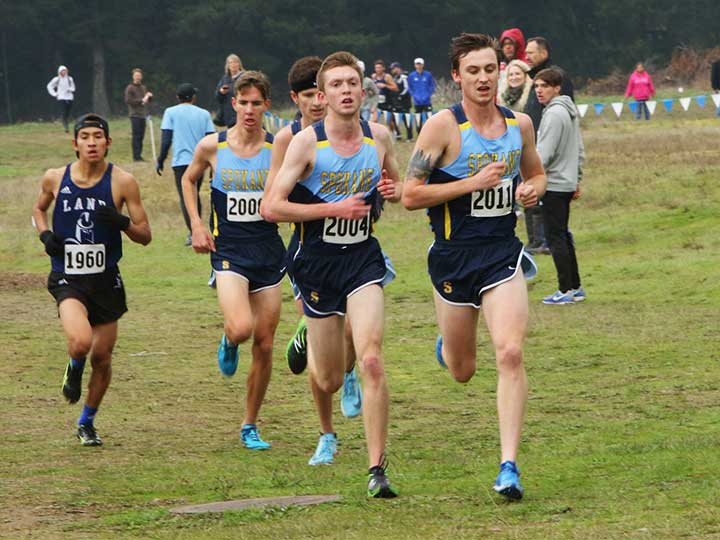 Men's cross country team running as a group on grass