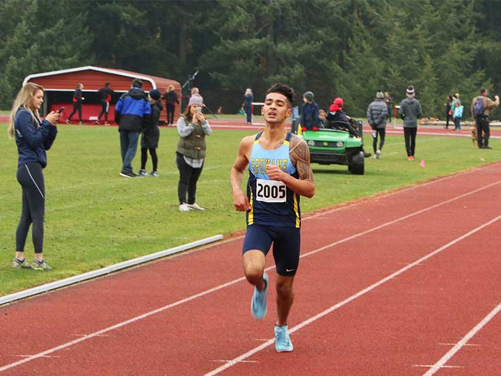 Men's cross country athlete running towards the finish