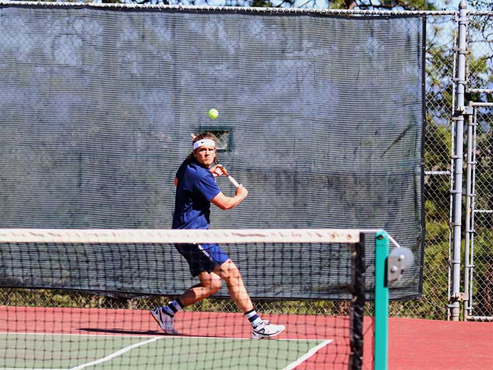 Men's tennis player hitting the ball with a back swing