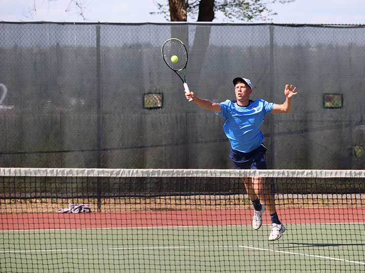 Men's tennis player striking the ball over the net
