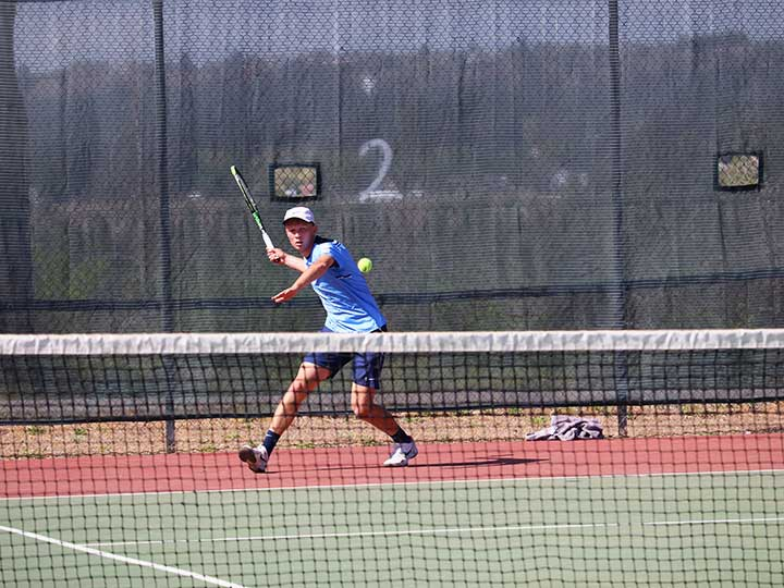 Men's tennis player running to hit the ball