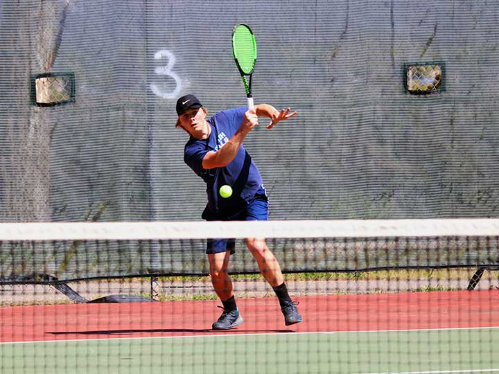 Men's tennis player with green racket returning the ball