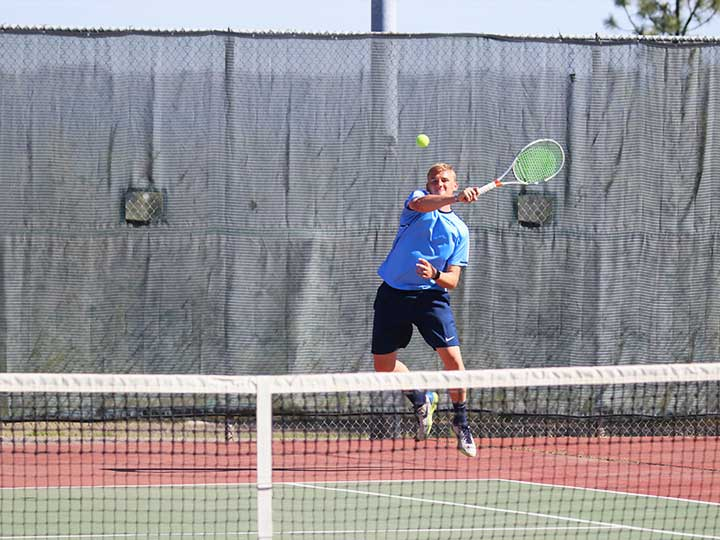 Men's tennis player jumping to return the ball over the net