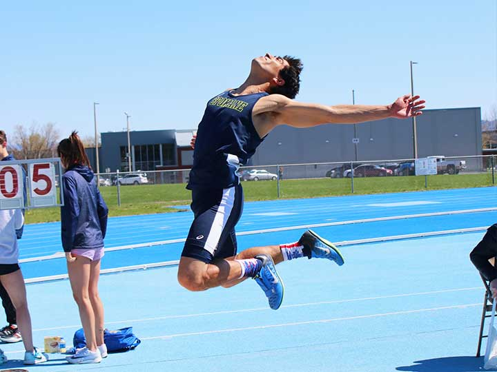 Men's track and field long jumper in mid air