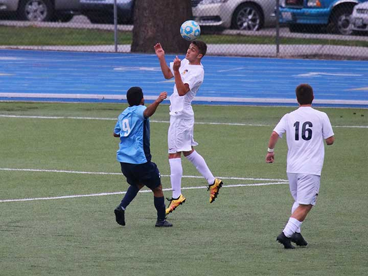 Men's soccer player head butting the ball