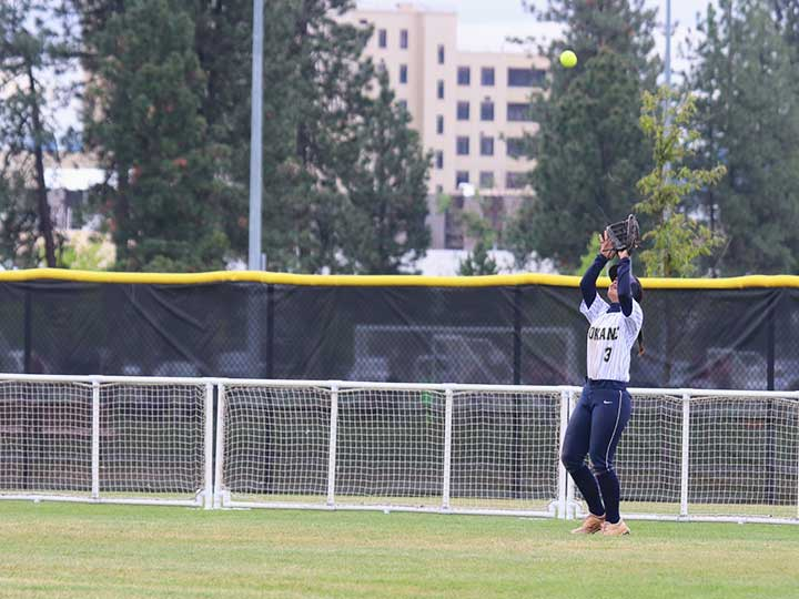 Softball outfield player catching the ball