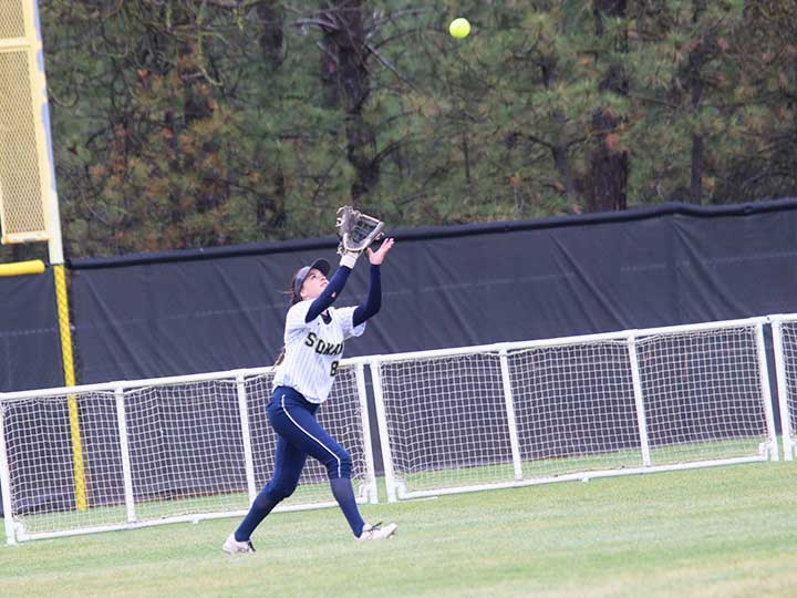 Softball player running to catch the ball in the outfield