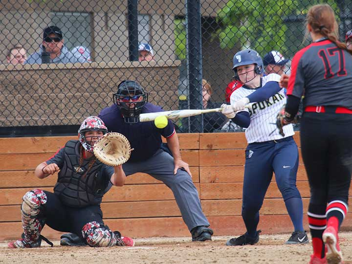 Softball player batting in mid swing with catcher in sight