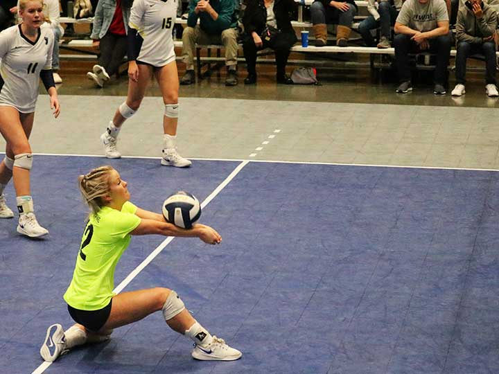 Volleyball player on one knee receiving the ball