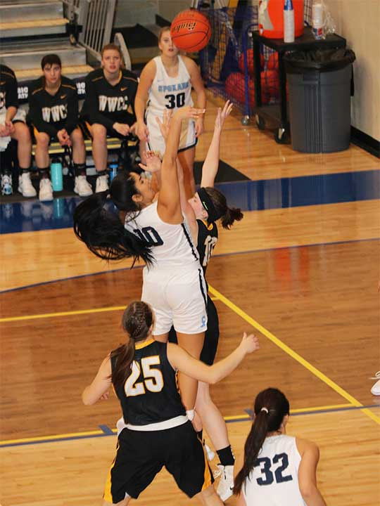 Women's Basketball player shooting for the hoop over opponents heads