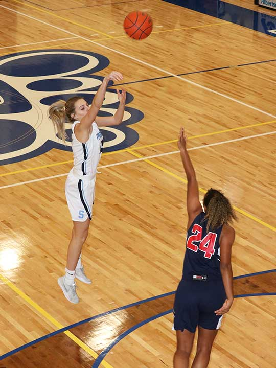 Women's basketball player shooting for the hoop from the three point line