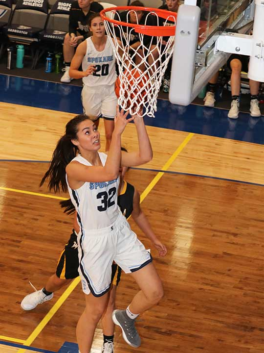 Women's basketball player going for the layup shot