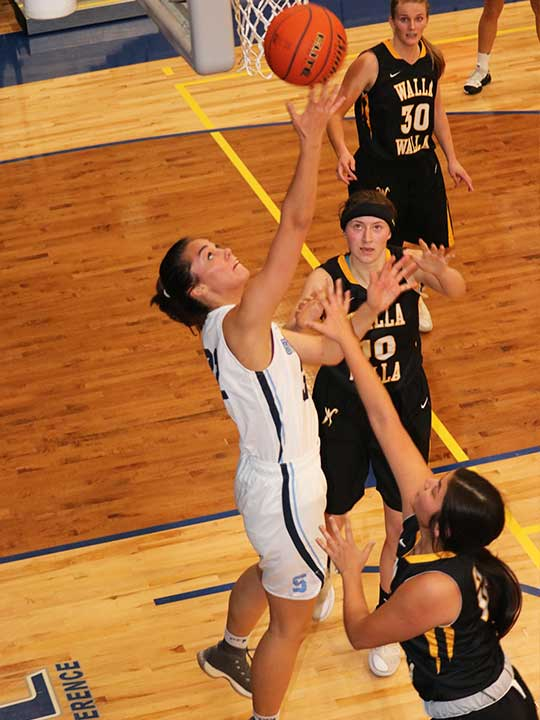 Women's Basketball player going for the layup backwards surrounded by opponents