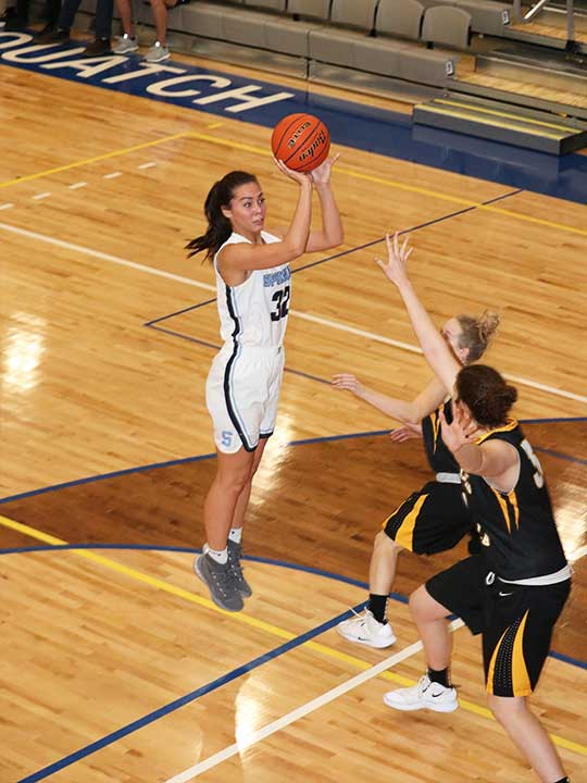 Women's basketball player in the air mid shoot on the hoop surrounded by opponents