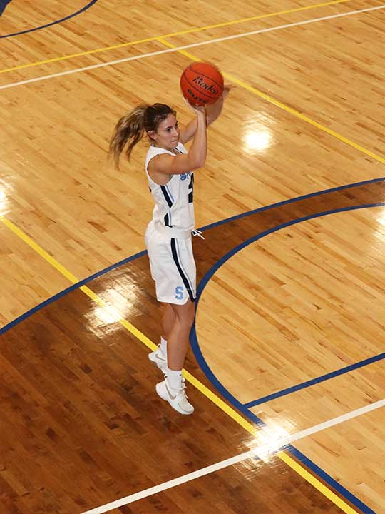 Women's basketball player shooting for the hoop in mid jump.