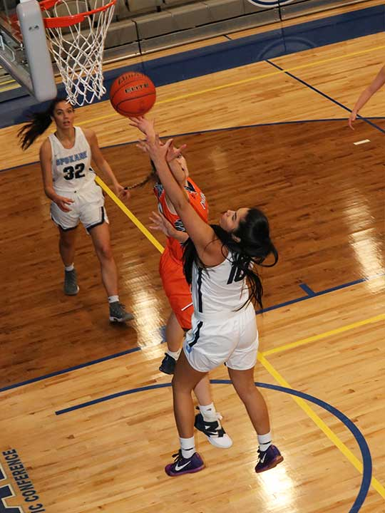 Women's basketball player shooting for the hoop against opponent