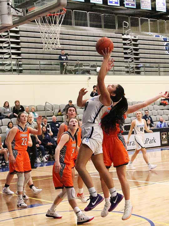 Women's basketball player jumping for the hoop while opponents watch