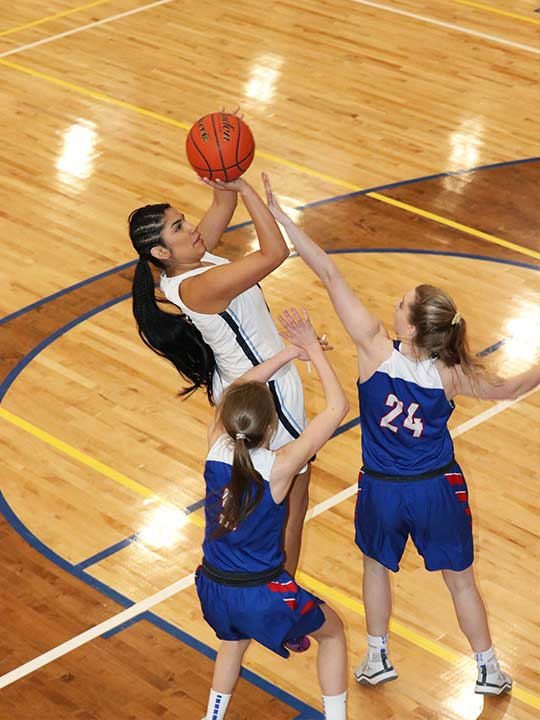 Women's Basketball player shooting for the hoop against two opponents.