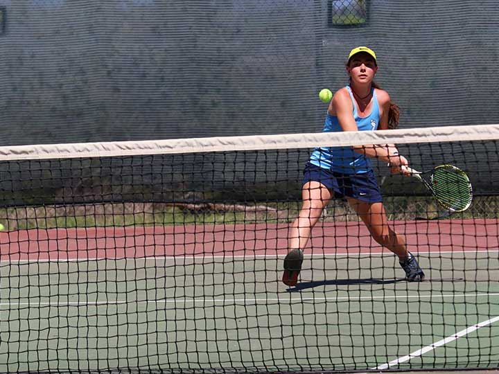 Women's tennis player stepping forward to return the ball