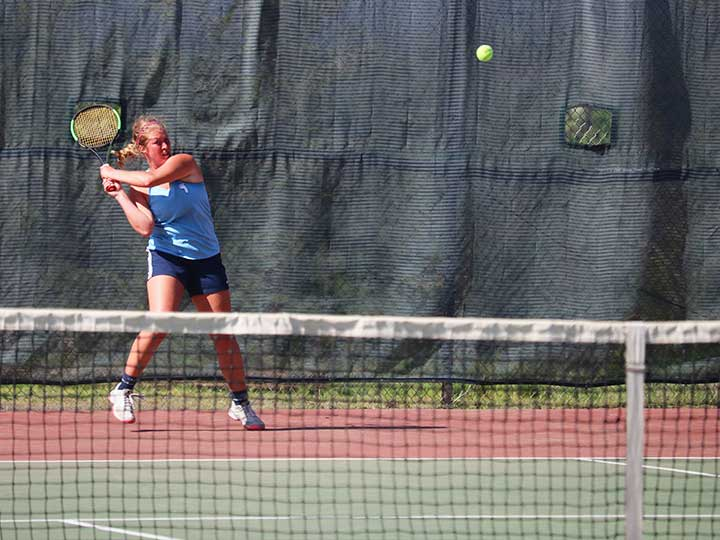 Women's tennis player aggressively preparing to return the ball
