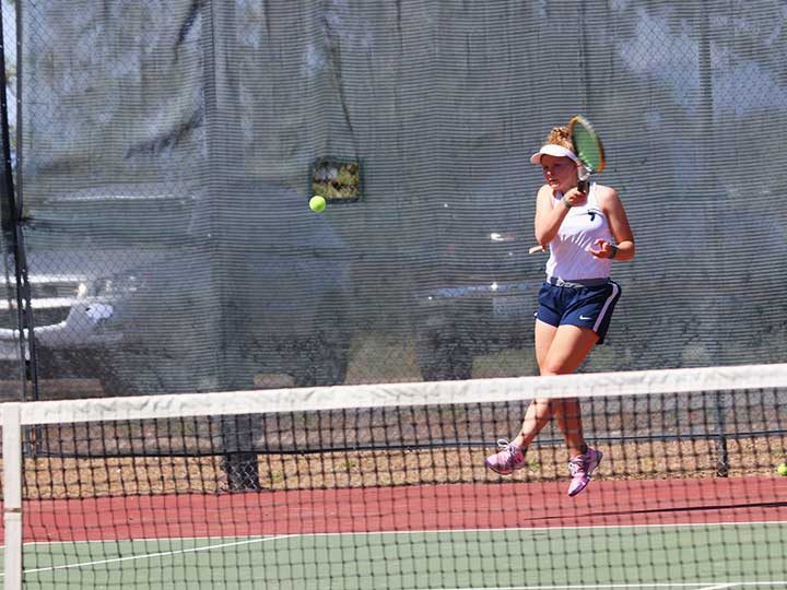 Women's tennis player returning the ball with one hand hit