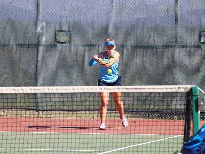 Women's tennis player returning the ball with and underhanded hit