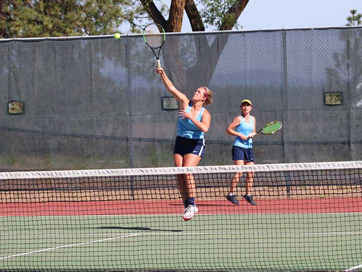 Women's tennis doubles player jumping to return the ball