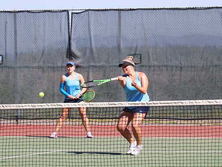 Women's tennis doubles player returning the ball with one hand underhand hit