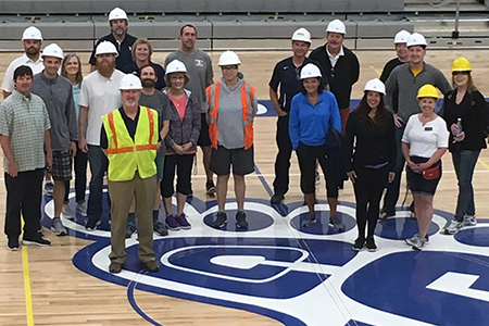 Group picture of coaches on the court with hard hats on.