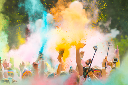A crowd throwing color powder in the air at a color run